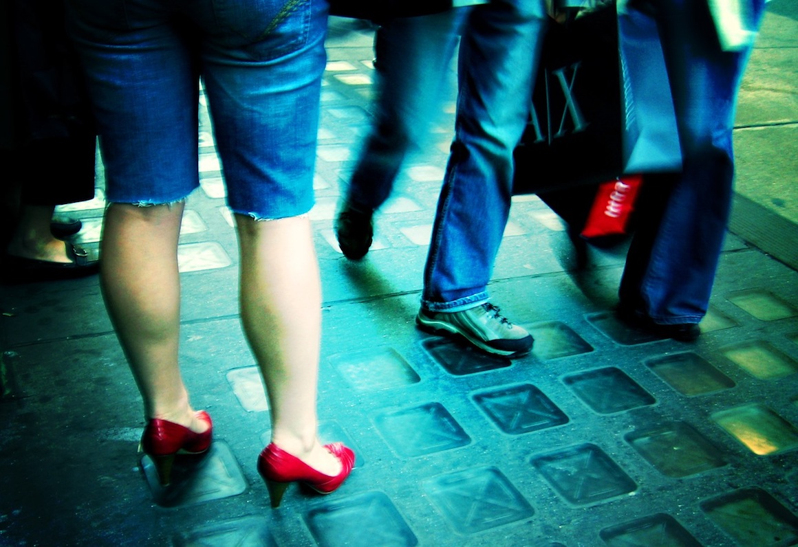 person in red heels standing on sidewalk