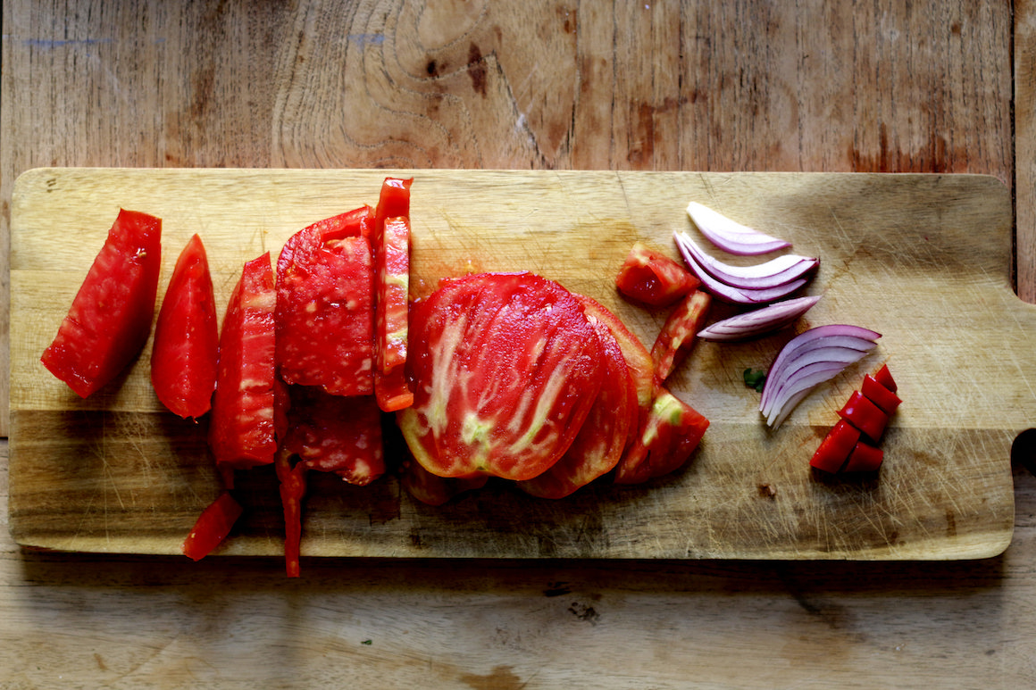 chopped tomatoes and red onions on a wooden cutting board