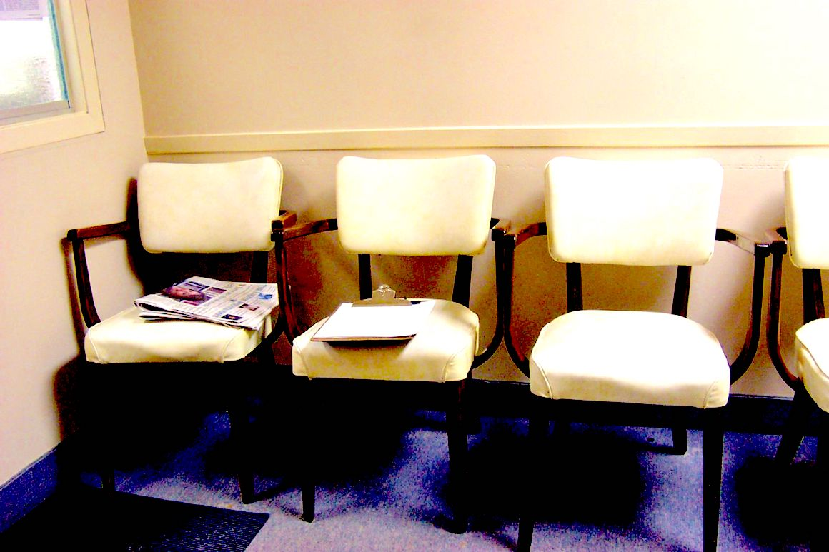 three white chairs in an empty waiting room