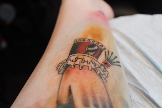 a close of up of a tattoo of a hand with a frilly cuff