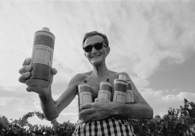 a skinny white man in sunglasses holding four bottles of liquid soap