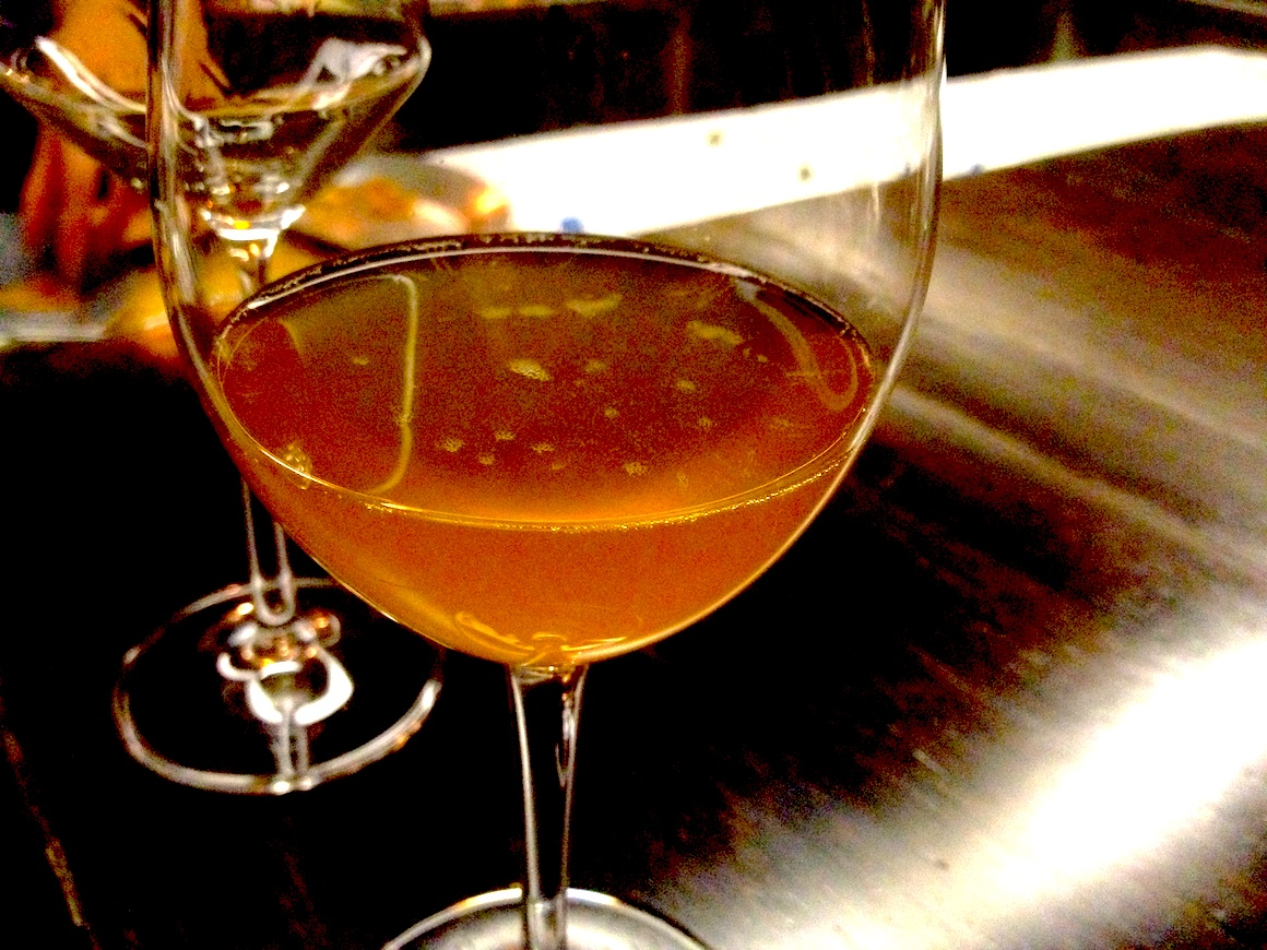 a glass of orange wine on a dark wood counter