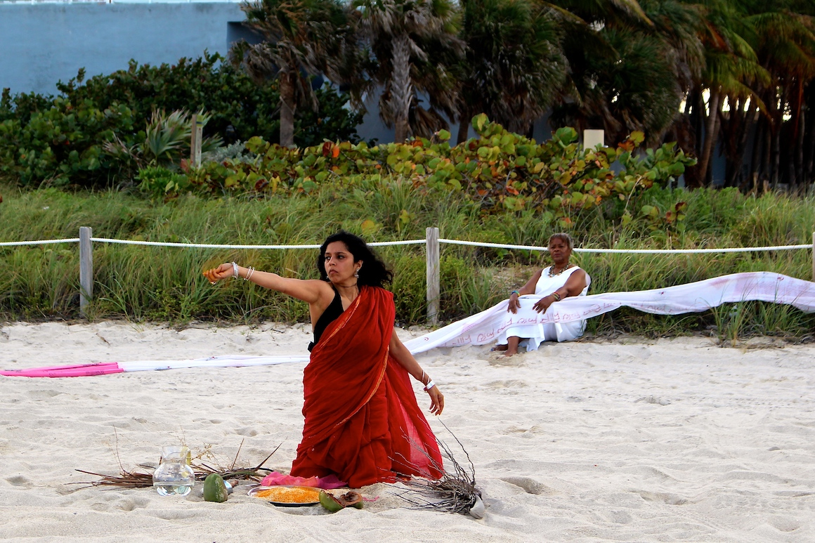 woman in red sari kneeling in the sand