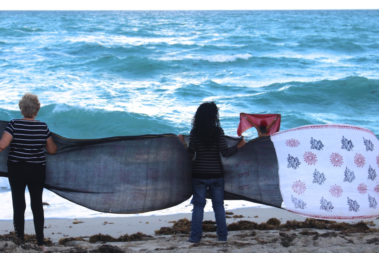 Women holding a lenth of sari, facing the ocean