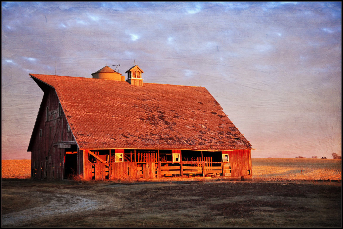 an abandoned barn in the middle of a field, at sunset