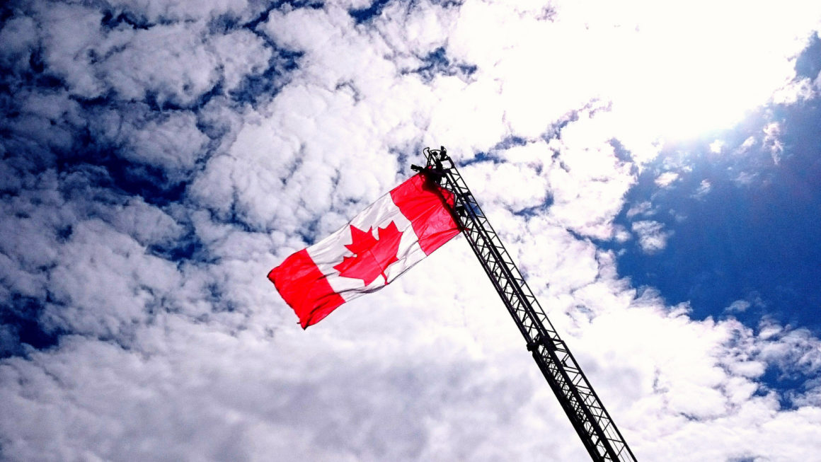 the canadian flag on a crane against a blue sky